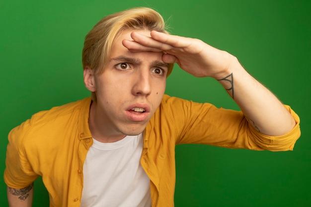 Verdächtiger blick auf den jungen blonden kerl der seite, der gelbes t-shirt trägt, das entfernung mit hand lokalisiert auf grün betrachtet