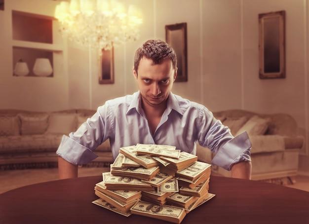 Verdächtiger geschäftsmann sitzt und schaut auf den geldhaufen