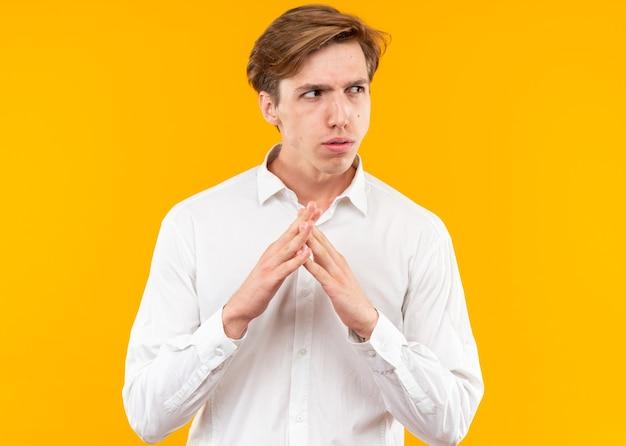 Verdächtiger junger gutaussehender kerl mit weißem hemd, das die hände zusammenhält, isoliert auf oranger wand?