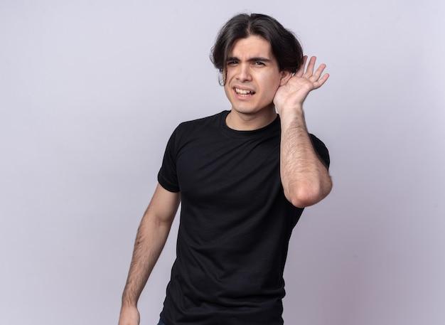 Verdächtiger junger hübscher kerl, der schwarzes t-shirt trägt, das auf weiße wand lokalisierte abhörgeste zeigt
