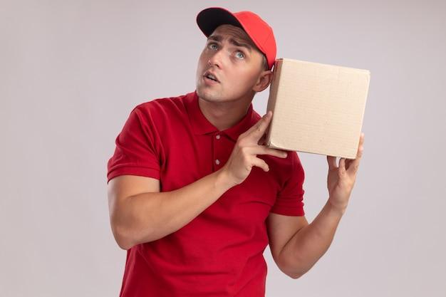 Verdächtiger junger lieferbote, der uniform mit mütze hält und box auf weißer wand isoliert hört