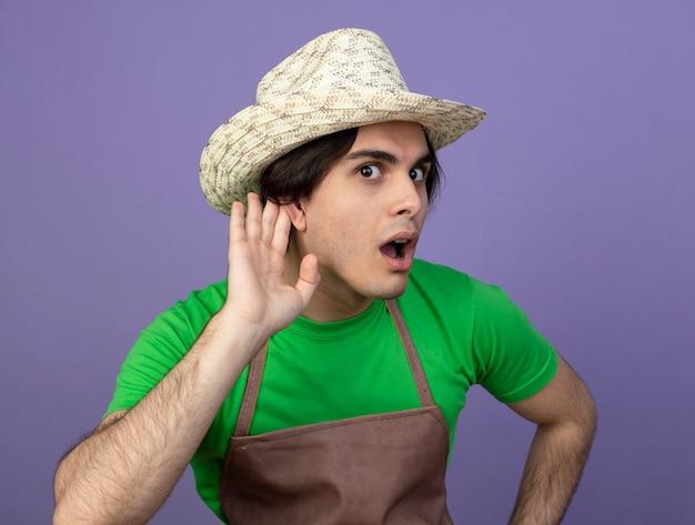 Verdächtiger junger männlicher gärtner in der uniform, die gartenhut trägt, der hörende geste zeigt