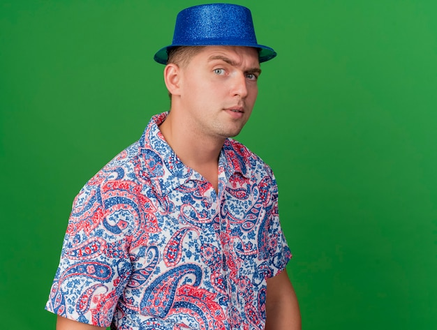 Verdächtiger junger party-typ, der blauen hut trägt, lokalisiert auf grün