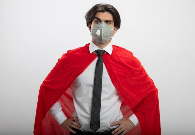 Verdächtiger junger superheld, der kamera betrachtet, die krawatte und medizinische maske trägt, die hände auf hüfte setzen
