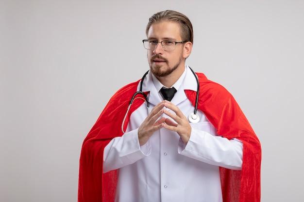 Verdächtiger junger superheldenmann, der medizinische robe mit stethoskop und brille hält, die hände zusammen lokalisiert auf weißem hintergrund halten