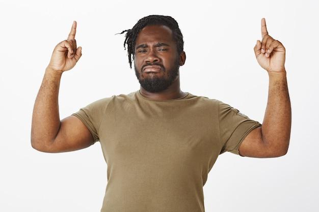 Verdächtiger kerl in einem braunen t-shirt, das gegen die weiße wand aufwirft