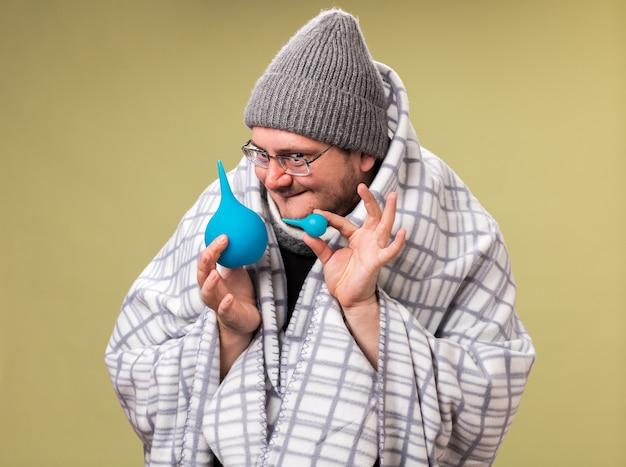 Verdächtiger kranker mann mittleren alters mit wintermütze und schal, der in karierte einläufe gehüllt ist