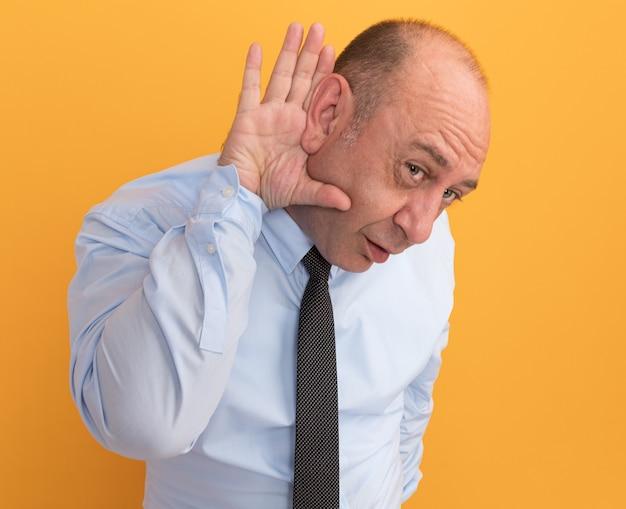 Verdächtiger mann mittleren alters, der weißes t-shirt mit krawatte trägt, die auf orange wand lokalisierte abhörgeste zeigt