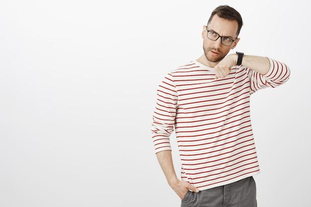 Verdächtiges ernstes hübsches männliches model in brille, hand in der nähe des ohrs haltend und beobachtend, über graue wand stehend, prüfend, ob das gerät richtig funktioniert