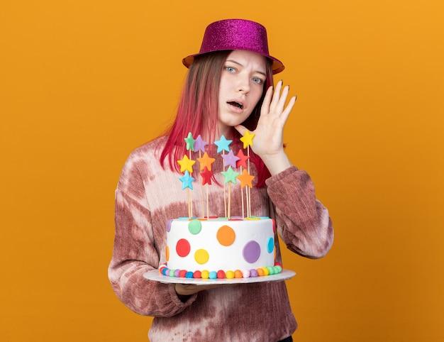 Verdächtiges junges schönes mädchen mit partyhut, das kuchen hält, flüstert isoliert auf oranger wand