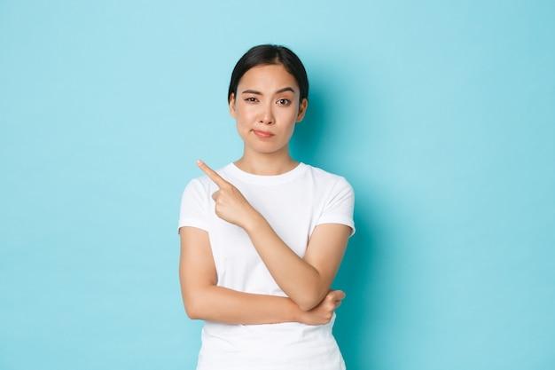 Verdächtiges und skeptisches schönes asiatisches mädchen im weißen t-shirt, das finger oben links zeigt