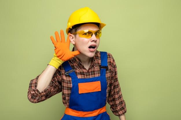 Verdächtiges zeigen hört geste junger männlicher baumeister, der uniform und handschuhe mit brille trägt