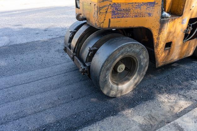 Verdichtungsgerätgummireifen rollt vibrierende asphaltstraßenbaustelle.