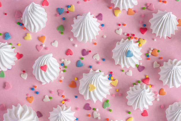 Verdrehte meringues mit süßwarendekorationen auf rosa hintergrund.