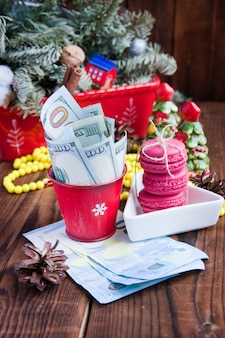Verdrehte rechnungen von dollar und von euro im roten weihnachtseimer, im euro und in den rosa makronen