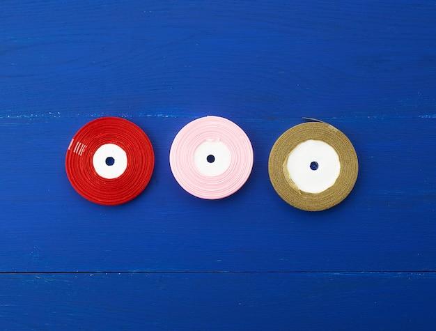 Verdrehte rote, rosa, goldene seidenbänder auf einem blauen hintergrund