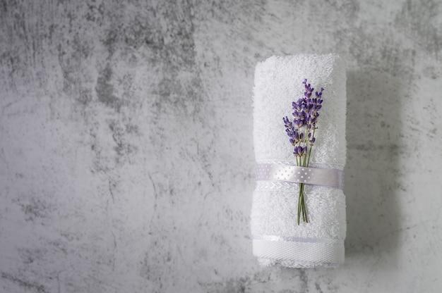 Verdrehtes badetuch mit lavendel auf hellgrauem. minimalismus, weichzeichnung, copyspace. spa.