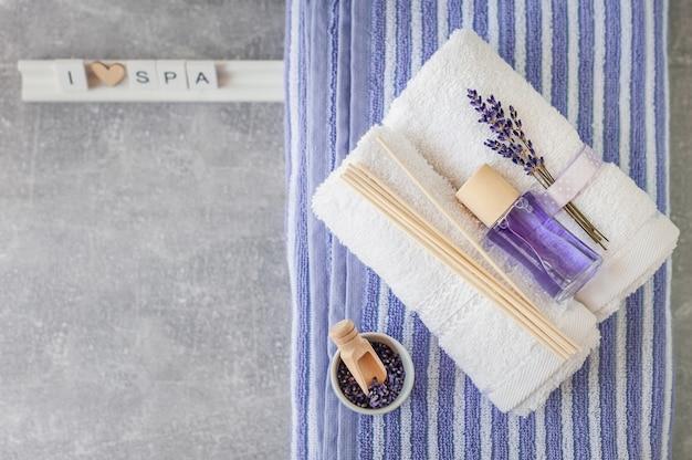 Verdrehtes badetuch mit lufterfrischer auf hellgrau.