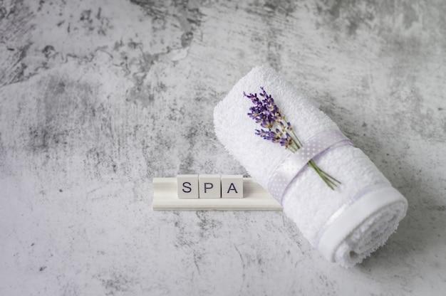 Verdrehtes badtuch mit lavendel- und holzbuchstabenrechtschreibung