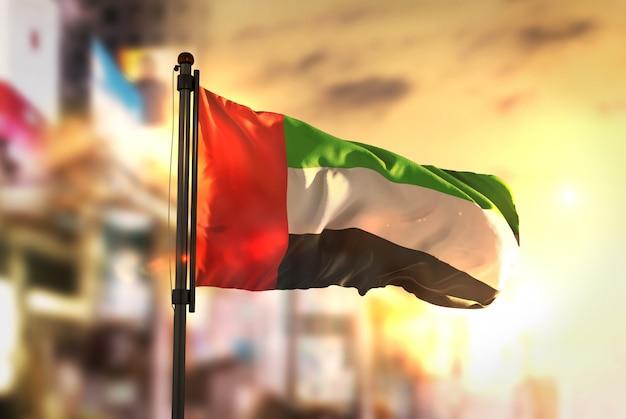Vereinigte arabische emirate flagge gegen stadt unscharfen hintergrund bei sonnenaufgang hintergrundbeleuchtung