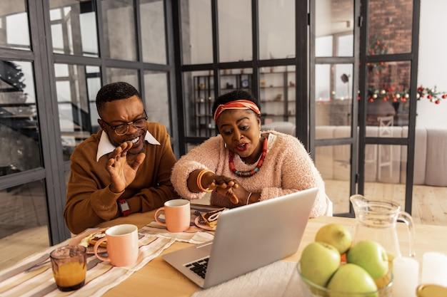 Vereinigte familie. glücklicher positiver bruder und schwester, die vor dem laptop sitzen, während sie mit ihrer familie sprechen