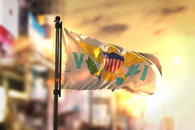 Vereinigte staaten virgin islands flagge gegen stadt verschwommen hintergrund bei sonnenaufgang hintergrundbeleuchtung