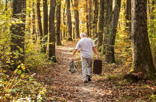 Vereint mit der natur. wochenende in der natur. urlaub und entspannung. ruhestand konzept. ältere menschen. reifer mann mit weißem bart im wald. hobby und freizeit. großvater mit vintage-koffer in der natur.