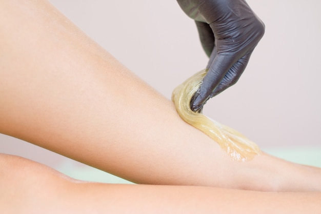 Verfahren der haarentfernung am bein schöne frau mit zuckerpaste oder wachshonig und schwarze handhand