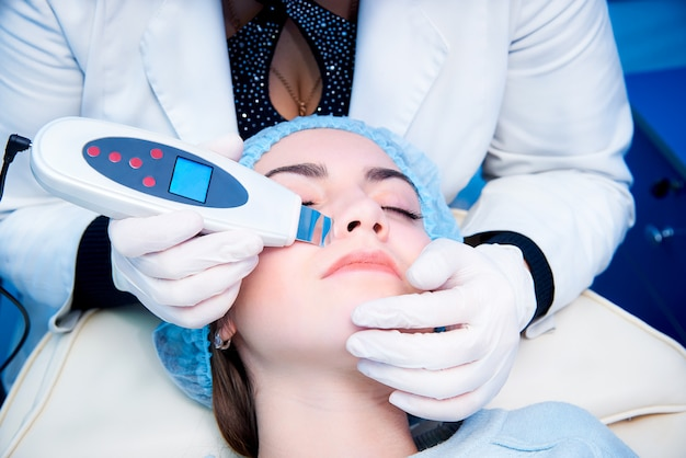 Verfahren der ultraschallreinigung des gesichts. ultraschallwäscher. konzept der medizinischen behandlung und hautpflege.