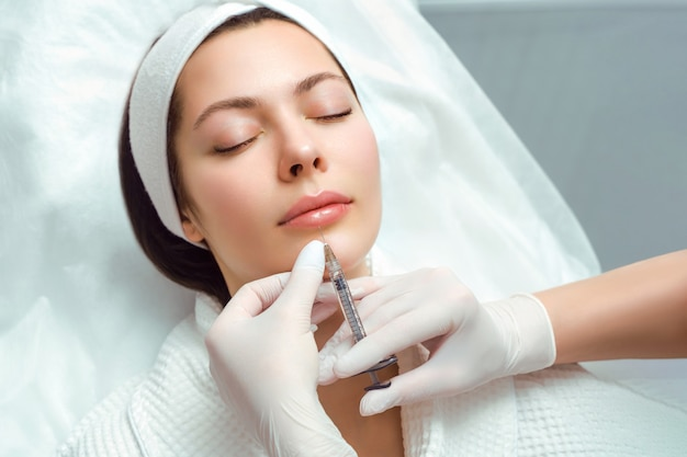 Verfahren zur lippenvergrößerung und -korrektur in einem kosmetiksalon. der spezialist macht eine injektion Premium Fotos