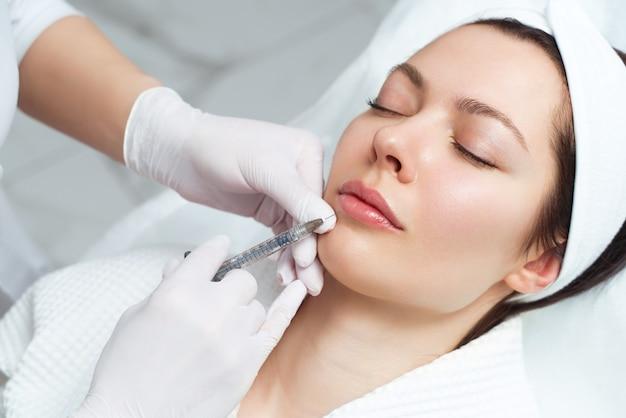 Verfahren zur lippenvergrößerung und -korrektur in einem kosmetiksalon. der spezialist macht eine injektion