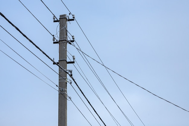 Verflechten von elektrischen drähten mit lichtern gegen den himmel. silhouette einer säule