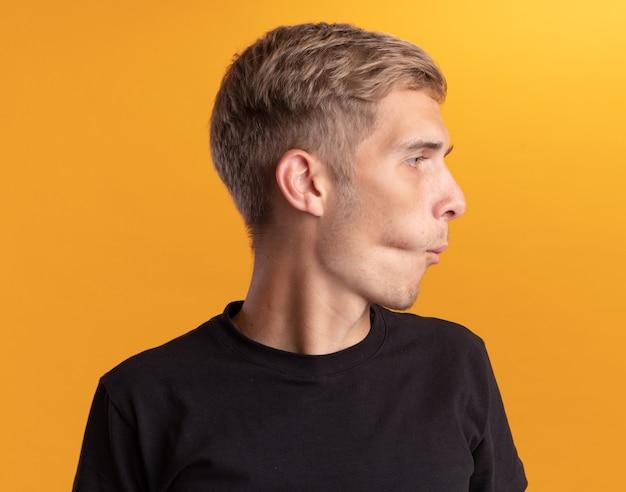 Verfolgende lippen, die den jungen gutaussehenden mann der seite betrachten, der das schwarze hemd trägt, das auf gelber wand lokalisiert wird
