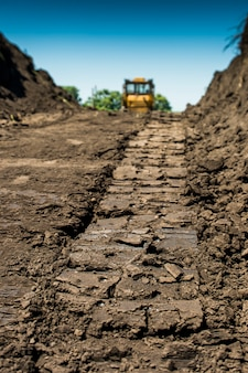Verfolgt gelben bulldozer mit raupentraktor, der in einem feld steht