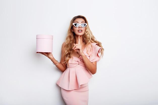 Verführerische blonde frau, die geschenkbox hält und im rosa kleid über weißer wand aufwirft. shopping und feiern konzept. modische sonnenbrille.