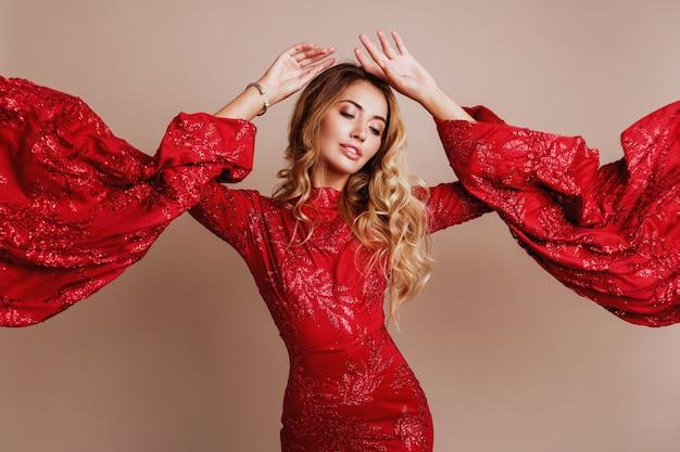 Verführerische blonde frau, die im roten luxuskleid mit weiten ärmeln aufwirft. modischer look. blonde wellige haare. ausdrucksstarkes foto. windiges tuch.