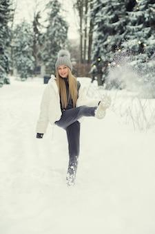 Verführerische blonde frau, die mit schnee im wald spielt