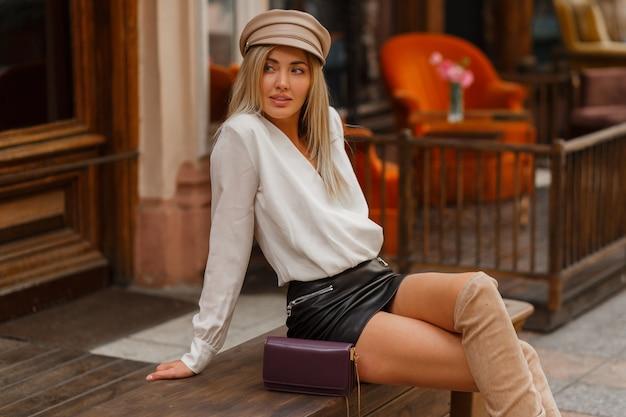 Verführerische blonde frau mit perfekten beinen, die auf bank sitzen