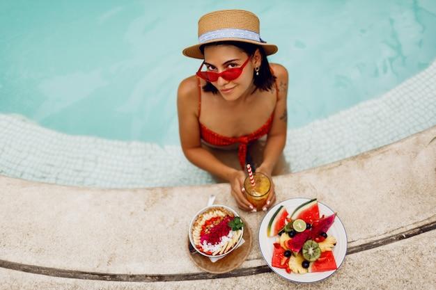 Verführerische brünette bräunungsfrau in den roten katzenaugen-sonnenbrillen und im strohhut, die im pool mit platte der exotischen früchte während des tropischen urlaubs entspannen. stilvolles tattoo.