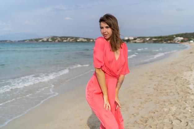 Verführerische brünette frau mit tätowierung zur hand im rosa kleid, das auf dem strand aufwirft.