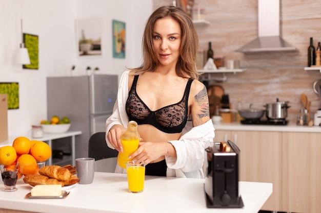 Verführerische frau, die ein köstliches und gesundes frühstück mit sexy schwarzer unterwäsche zubereitet. junge sexy verführerische blondine mit tattoos trinkt gesunden, natürlichen hausgemachten orangensaft,