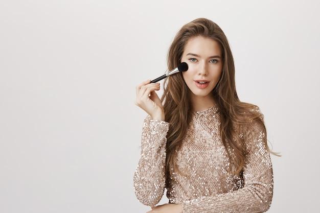 Verführerische frau, die gesicht mit make-up-pinsel berührt