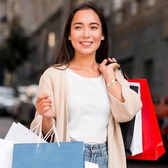 Verführerische frau, die mit einkaufstaschen und verkaufssitzung aufwirft
