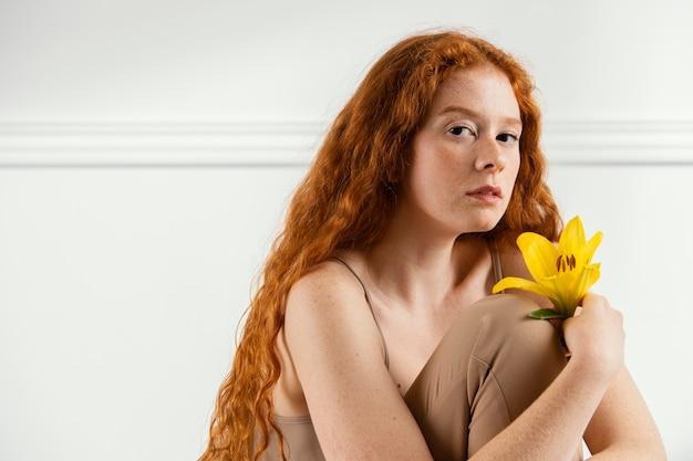 Verführerische frau, die mit frühlingsblume aufwirft