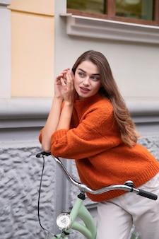 Verführerische frau, die mit ihrem fahrrad in der stadt aufwirft
