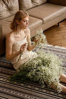 Verführerische frau, die neben sofa sitzt, während frühlingsblumen halten