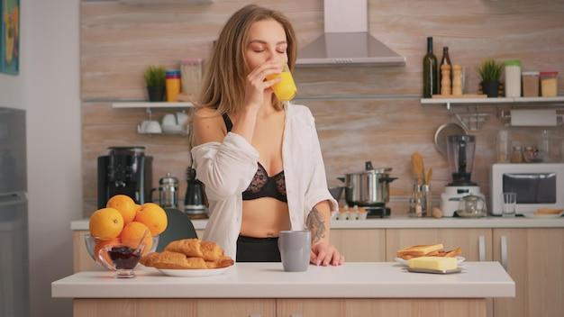 Verführerische frau in sexy unterwäsche genießt den morgen und trinkt ein glas frischen orangensaft in der küche. junge blonde dame mit tätowierungen in schwarzen dessous, erfrischender sonntagmorgen