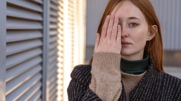 Verführerische frau posiert, während sie ihr halbes gesicht mit der hand bedeckt