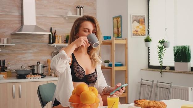 Verführerische hausfrau mit tattoos mit smartphone, die temping-unterwäsche trägt und morgens kaffee trinkt. attraktive blonde dame in dessous, die während des frühstücks eine tasse tee hält und die zeit genießt.