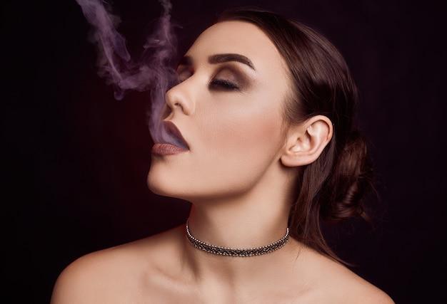 Verführerische herrliche brunettefrau des zaubers, die elektronische zigarette raucht